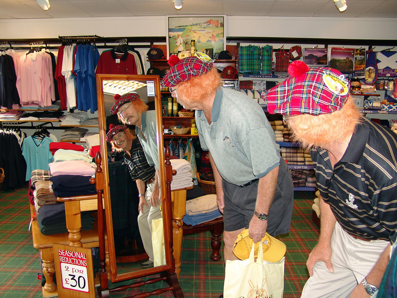 Trying on Scottish caps in St. Andrews shop.   2009
