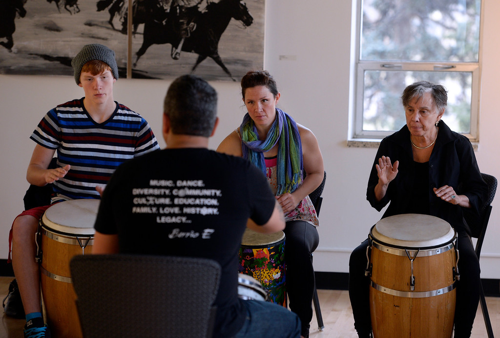 . DENVER, CO - FEBRUARY 15: Students from left Smith Nagel, 14, his mother Rachel, and Juana Bordas watch carefully the drumming technique of their instructor Jose Daniel Beteta. Co-founders of Barrio E, Tamil Maldonado and husband Jose Daniel Beteta, gather students together at the McNichols Building in downtown Denver to teach a Bomba workshop. Bomba is an Afro-Caribbean rhythm with percussion, dance and song. Barrio E is a project based in Boulder that hopes to serve communities around Colorado and aims to expose, educate, and promote traditional Puerto Rican culture and music. Barrio E\'s next workshop for both kids and adults at McNichols will be Saturday, Mar. 15, 2014. (Photo by Kathryn Scott Osler/The Denver Post)