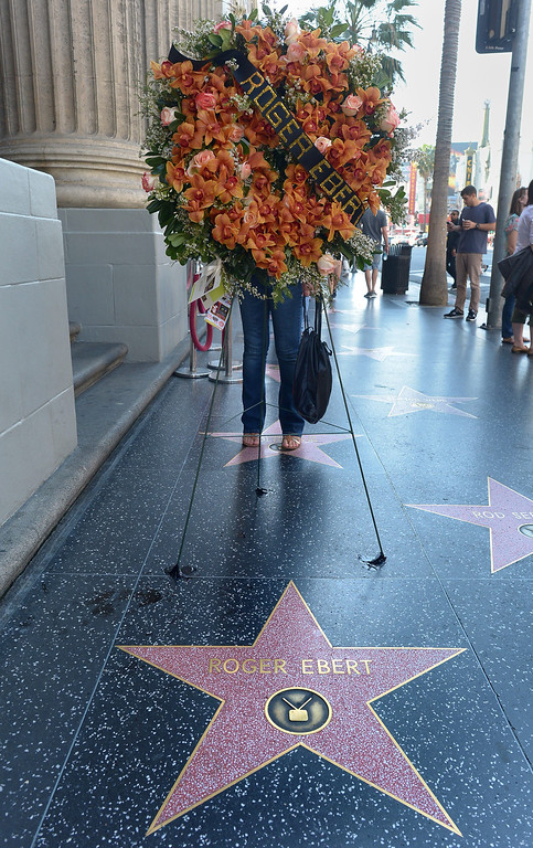 . Flowers are placed before the Star for Roger Ebert on Hollywood\'s Walk of Fame April  4, 2013 in Hollywood,California.  Ebert, the first film critic to win a Pulitzer Prize, died April 4, 2013, the US newspaper that employed him for more than four decades said. He was 70.  Ebert -- who just two days ago announced in a blog post that he was taking a break from his main job -- succumbed to cancer after a long battle, according to the Chicago Sun-Times.     AFP PHOTO / JOE KLAMAR        (Photo credit should read JOE KLAMAR/AFP/Getty Images)