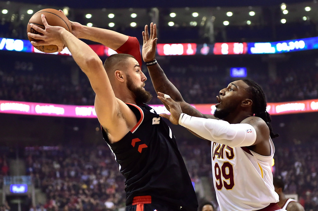 . Toronto Raptors center Jonas Valanciunas (17) looks to pass the ball over Cleveland Cavaliers forward Jae Crowder (99) during the first half of an NBA basketball game Thursday, Jan. 11, 2018, in Toronto. (Frank Gunn/The Canadian Press via AP)
