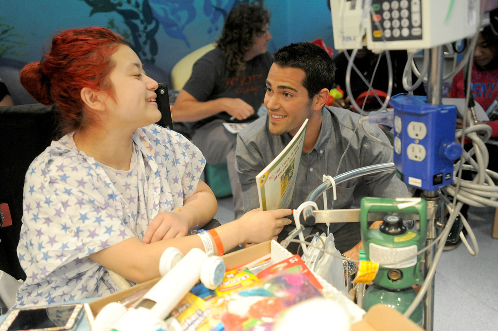 ". 04-18-2013-(LANG Staff Photo by Sean Hiller)-Toyota Grand Prix Celebrities visited Miller�s Children�s Hospital to visit the children they are raising money for through ""Racing for Kids.\""  Celebrity driver Jesse Metcalfe visits with patient Cynthia Fuentes at Thursday\'s event."