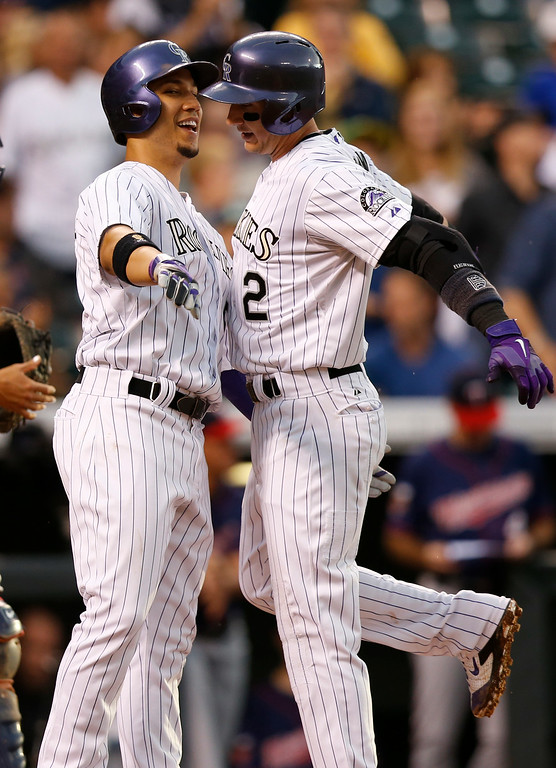 . Colorado Rockies\' Troy Tulowitzki (2) and Carlos Gonzalez (5) chest bump after scoring on Tulowitzki\'s two run home run hit off Minnesota Twins starting pitcher Kris Johnson during the third inning of a baseball game on Friday, July 11, 2014, in Denver. (AP Photo/Jack Dempsey)