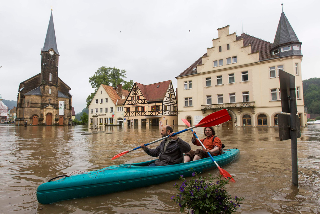 . Two men paddle across a flooded market square after the Elbe river broke its banks during a flood in the east German town of Wehlen in the federal state of Saxony June 4, 2013. REUTERS/Thomas Peter