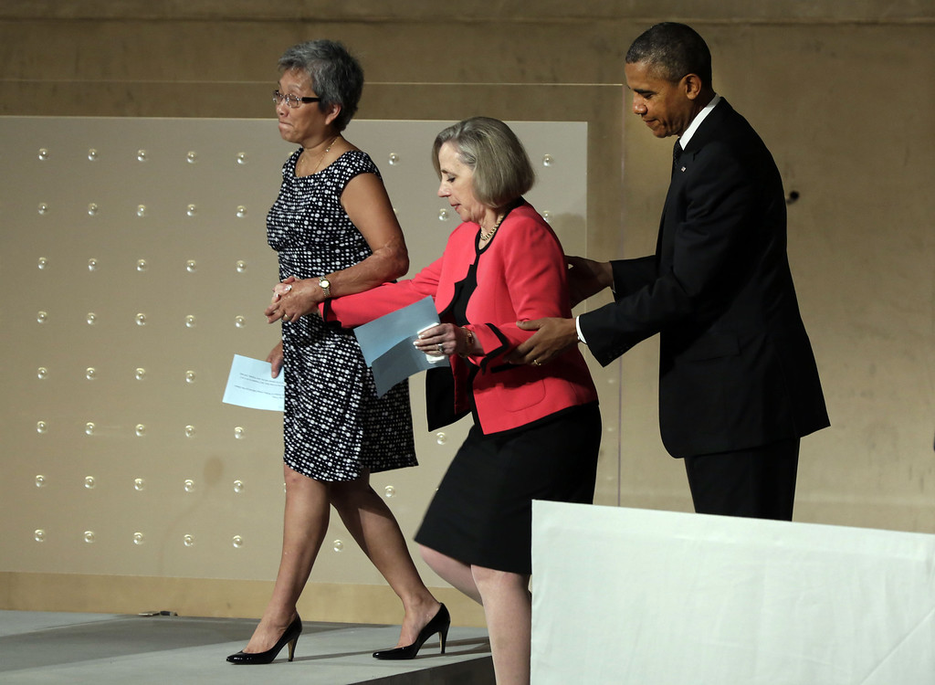 . President Barack Obama (R) assists Ling Young (L) and Alison Crowther to the platform to speak during the dedication ceremony in Foundation Hall at the National September 11 Memorial Museum at ground zero May 15, 2014 in New York City. Young was working on the 86th floor of the South Tower and was one of 12 people who escaped the sky lobby after Flight 175 struck the World Trade Center. Crowther is the mother of Welles Crowther who was killed on September 11 while assisting in the evacuation efforts in the South Tower.  (Photo by Richard Drew-Pool/Getty Images)