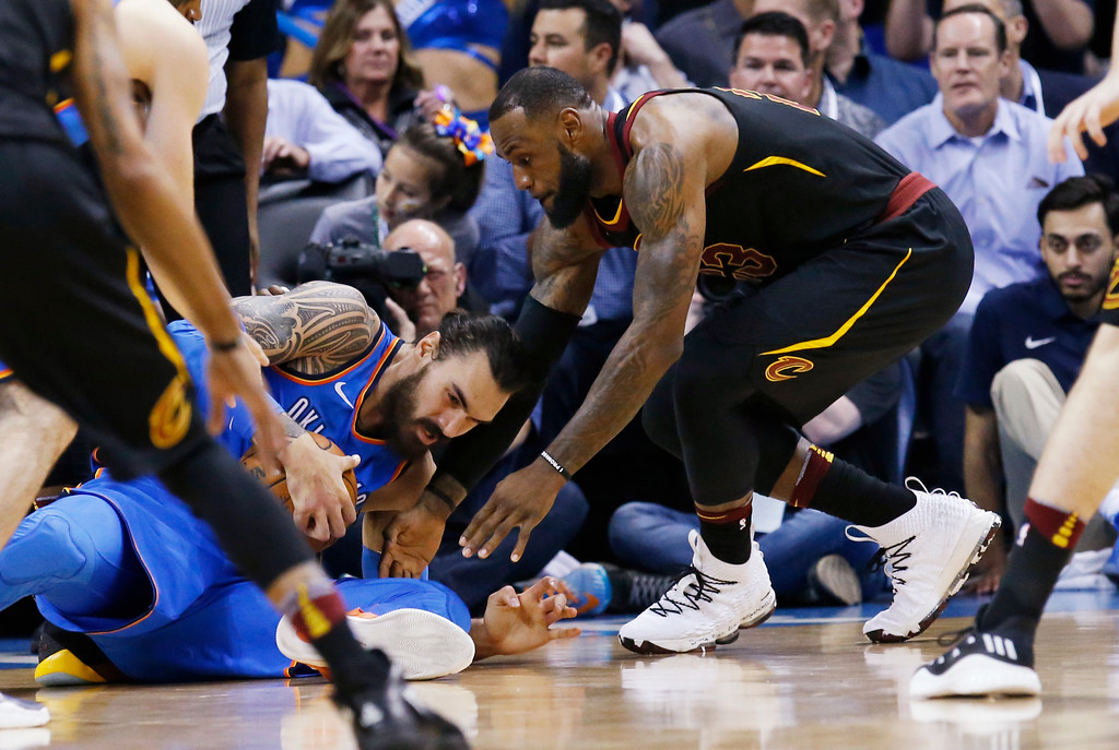 . Cleveland Cavaliers forward LeBron James, right, reaches in for the ball held by Oklahoma City Thunder center Steven Adams during the first half of an NBA basketball game in Oklahoma City, Tuesday, Feb. 13, 2018. (AP Photo/Sue Ogrocki)
