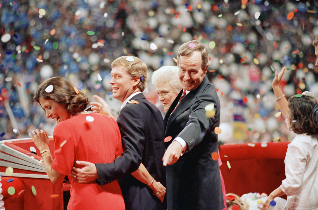 . Republican presidential candidate George Bush points behind the back of his running mate Sen. Dan Quayle of Indiana as they and their wives, Marilyn Quayle, left, and Barbara Bush are showered with confetti at the end of the Republican National Convention in New Orleans on August 18, 1988. (AP Photo/J. Scott Applewhite)