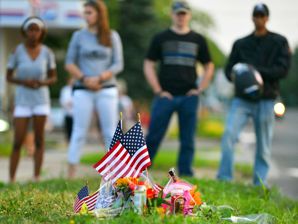 . Neighborhood residents look on at a makeshift memorial before a candlelight vigil in honor of slain Mendota Heights Police Officer Scott Patrick on Wednesday evening. (Pioneer Press: John Autey)