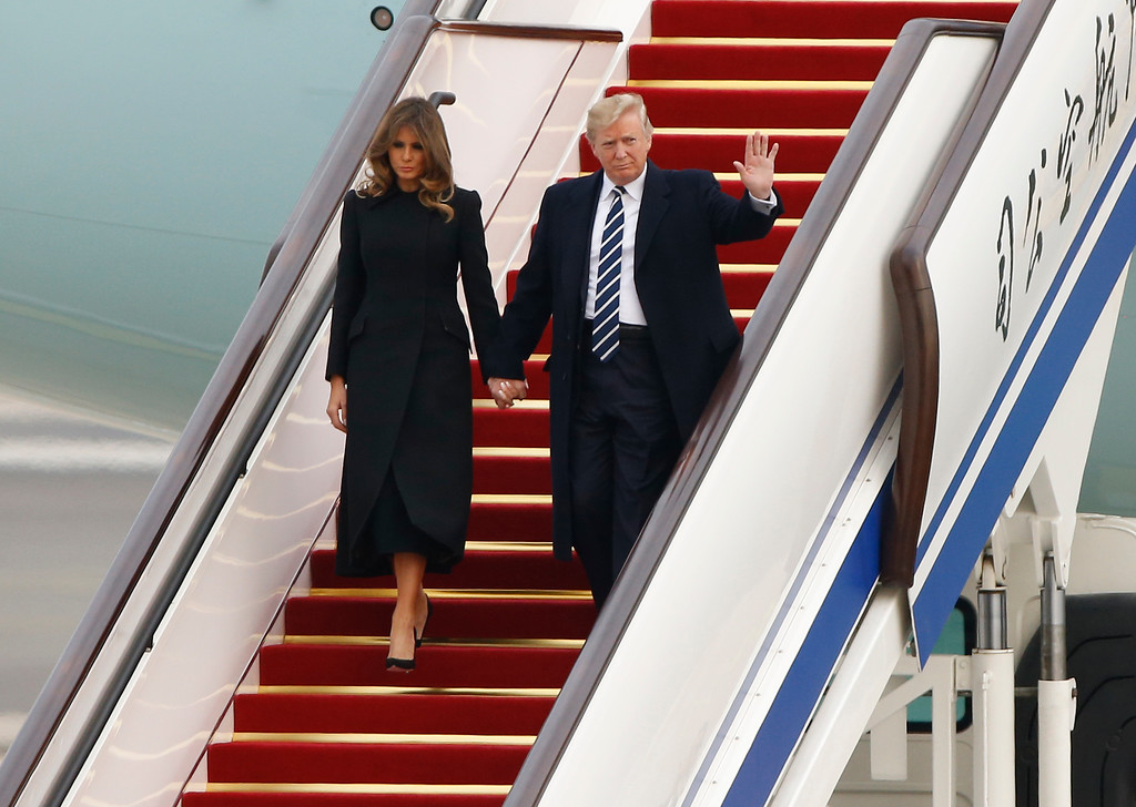. U.S. President Donald Trump, right, and first lady Melania Trump walk down the steps of Air Force One on their arrival at an airport in Beijing, China, Wednesday, Nov. 8, 2017. (Thomas Peter/Pool Photo via AP)