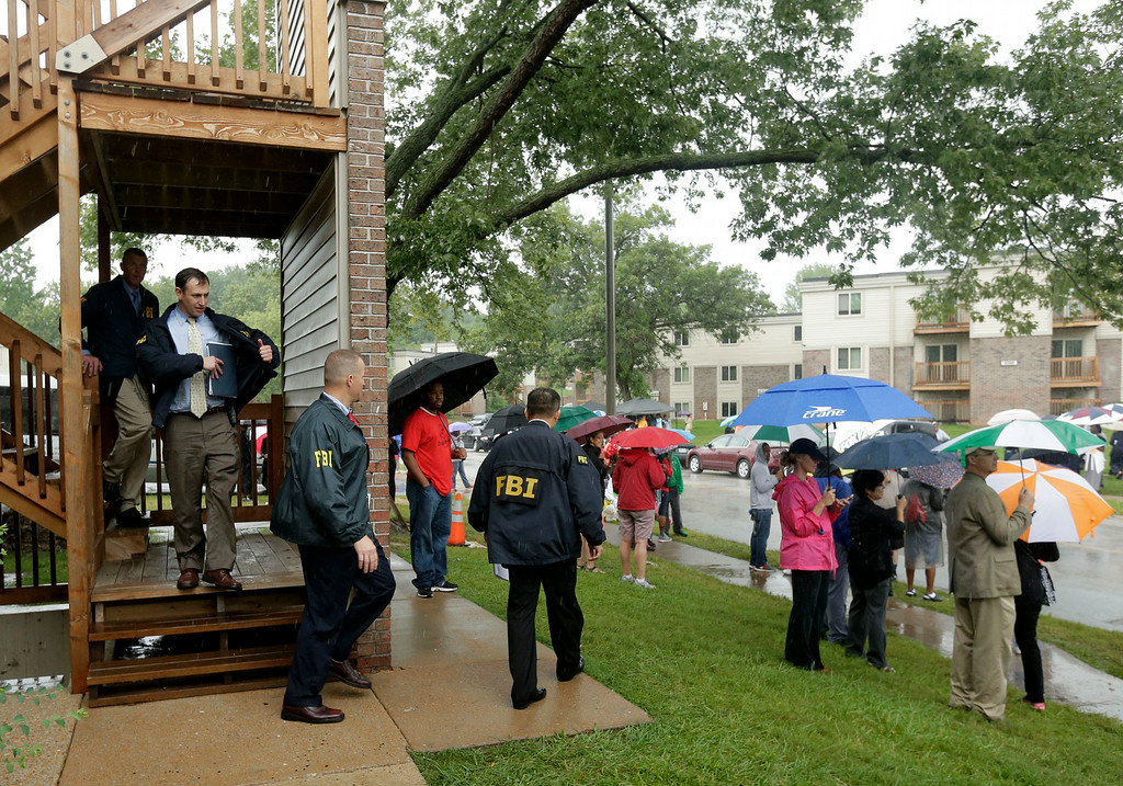 . FBI agents leave an apartment building adjacent to a makeshift memorial for Michael Brown on Saturday, Aug. 16, 2014, located at the site where Brown was shot by police a week ago in Ferguson, Mo. Brown\'s shooting in the middle of a street following a suspected robbery of a box of cigars from a nearby market has sparked a week of protests, riots and looting in the St. Louis suburb. (AP Photo/Charlie Riedel)