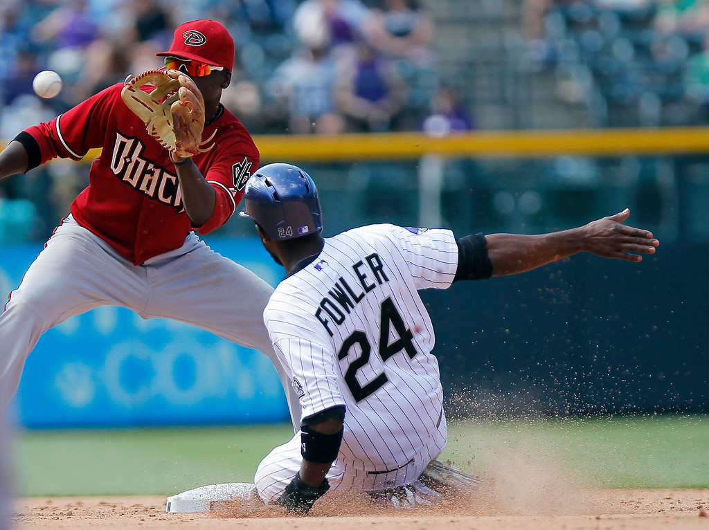 . Arizona Diamondbacks\' Didi Gregorius, left, can\'t make the play as Colorado Rockies\' Dexter Fowler (24) steals second base during the sixth inning of a baseball game Wednesday, May 22, 2013 in Denver. The Rockies won 4-1.(AP Photo/Barry Gutierrez)