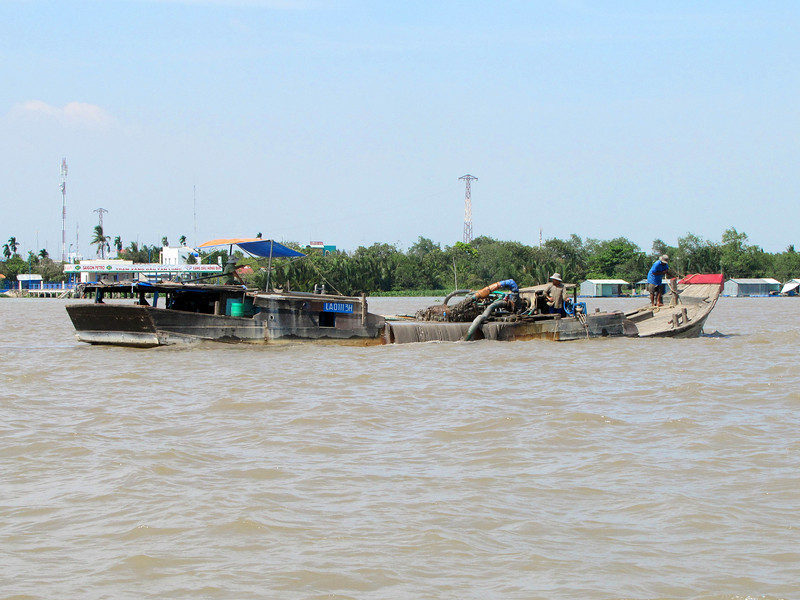 53-This ship harvests valuable building sand from the river. Along the major tributaries of the Mekong, many islands, roads, and residential areas are being whittled down because of illegal sand mining.