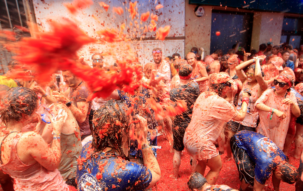 ". Revelers enjoy as they throw tomatoes at each other, during the annual ""Tomatina\"", tomato fight fiesta, in the village of Bunol, 50 kilometers outside Valencia, Spain, Wednesday, Aug. 30, 2017. At the annual \""Tomatina\"" battle, that has become a major tourist attraction, trucks dumped 160 tons of tomatoes for some 20,000 participants, many from abroad, to throw during the hour-long Wednesday morning festivities. (AP Photo/Alberto Saiz)"