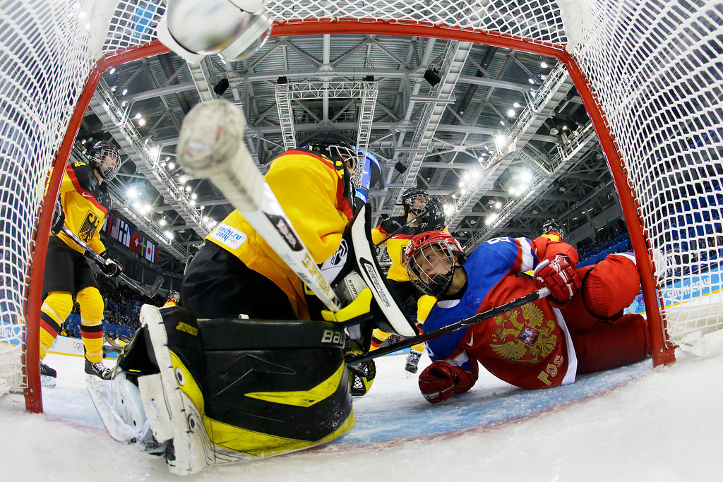 . Yekaterina Smolina of Russia looks up at Goalkeeper Viona Harrer of Germany after colliding in front of the goal in the first period of the women\'s ice hockey game at Shayba Arena the 2014 Winter Olympics, Sunday, Feb. 9, 2014, in Sochi, Russia. (AP Photo/Pool)