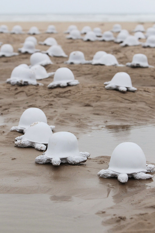 ". A picture taken in Colleville-sur-Mer Beach on June 5, 2011,shows part of the installation by French artist Rachid Khimoune of 1.000 turtle-shaped statues made in the 90\'s from diferent countries helmets. The statues, exhibited here on the 67th D-Day anniversary on June 6, 1944 allied landings in Normandy, then occupied by Nazi Germany, aim at symbolizing ""the never ending horrors of war\"". AFP  PHOTO  KENZO TRIBOUILLARD"