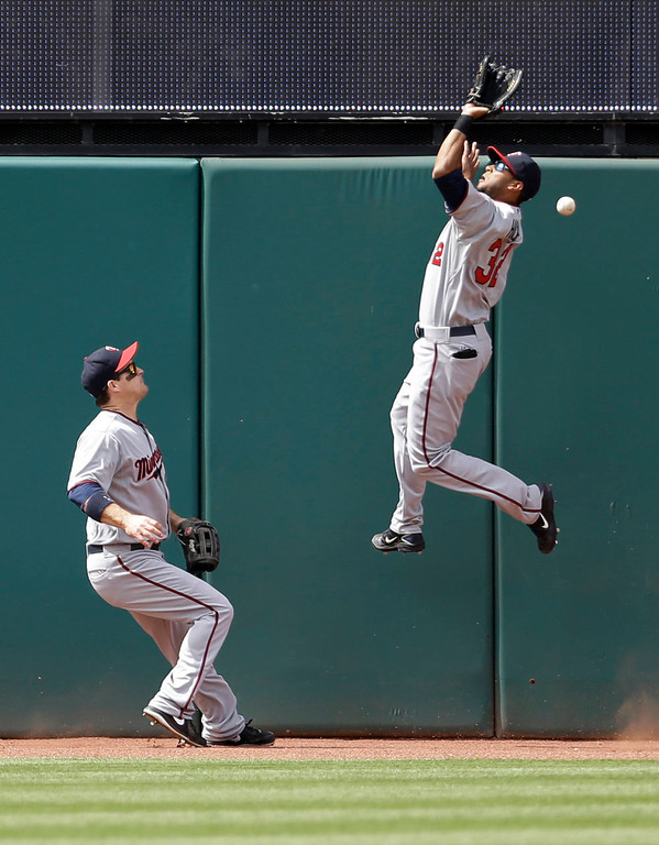 . Minnesota Twins\' Aaron Hicks, right, jumps but cannot get to a triple hit by Cleveland Indians\' Jason Kipnis in the seventh inning. Twins\' Josh Willingham backs up the play at left. (AP Photo/Tony Dejak)