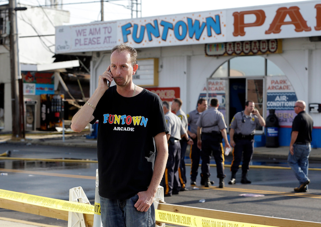 . Daniel Shauger, manager of the Funtown Arcade, talks on the phone near the establishment the morning after a massive fire burned a large portion of the Seaside Park boardwalk including the arcade, Friday, Sept. 13, 2013, in Seaside Park, N.J. (AP Photo/Julio Cortez)