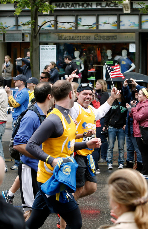 . Runners who were unable to finish the Boston Marathon on April 15 because of the bombings pass the first bombing site as they head toward the finish line on Boylston Street after the city allowed them to finish the last mile of the race in Boston Saturday, May 25, 2013. (AP Photo/Winslow Townson)