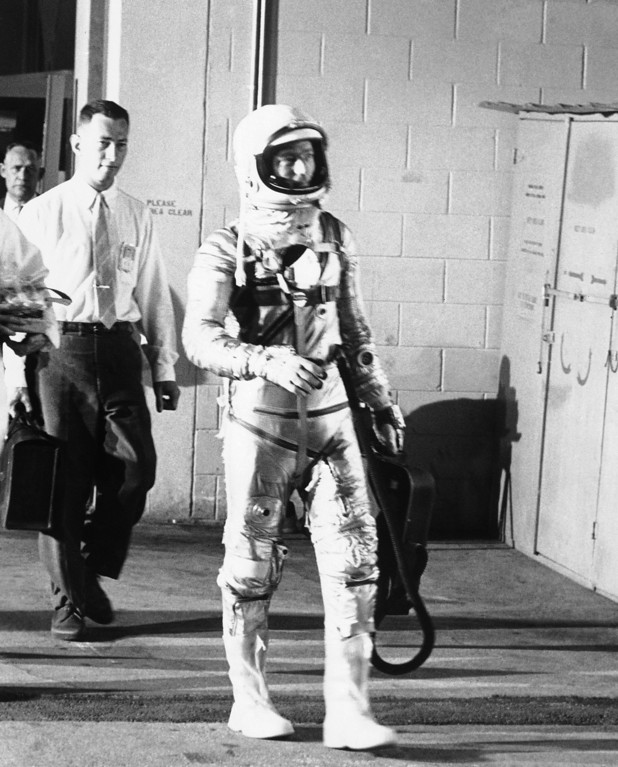 . Astronaut Scott Carpenter leaves Hanger S at Cape Canaveral, May 24, 1962 en route to van which took him to launching pad for his flight into space. He was scheduled to make a triple orbit of the earth. Carpenter is carrying his portable air conditioner. (AP Photo)