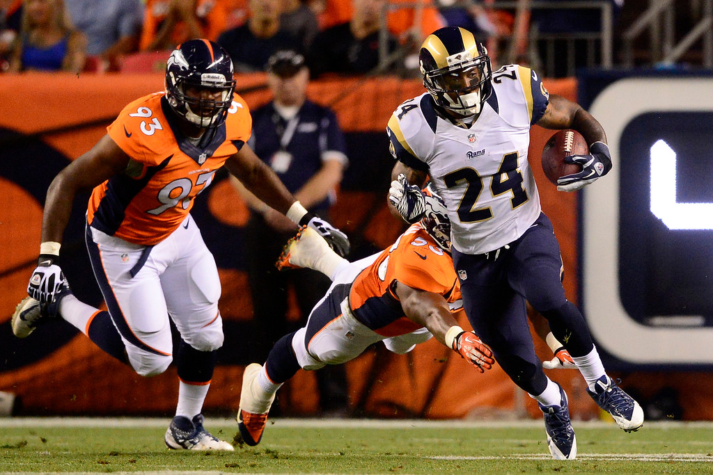 . DENVER, CO - AUGUST 24: Isaiah Pead (24) of the St. Louis Rams breaks into the open field on a run against the Denver Broncos during the second half of action of an NFL preseason game at Sports Authority Field at Mile High on August 24, 2013. This is the third game of the preseason for the Broncos. (Photo by AAron Ontiveroz/The Denver Post)