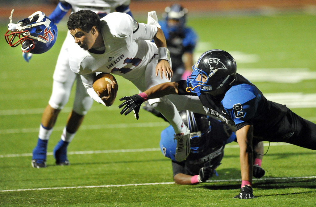 . Los Altos quarterback Cristian Hacegaba (#11) loses his helmet as he is hit by Diamond Ranch\'s Allen Salguero (#2) in their Hacienda League opener football game at Diamond Ranch High School in Pomona on Friday October 4, 2013. (San Gabriel Valley Tribune/Staff Photo by Keith Durflinger)