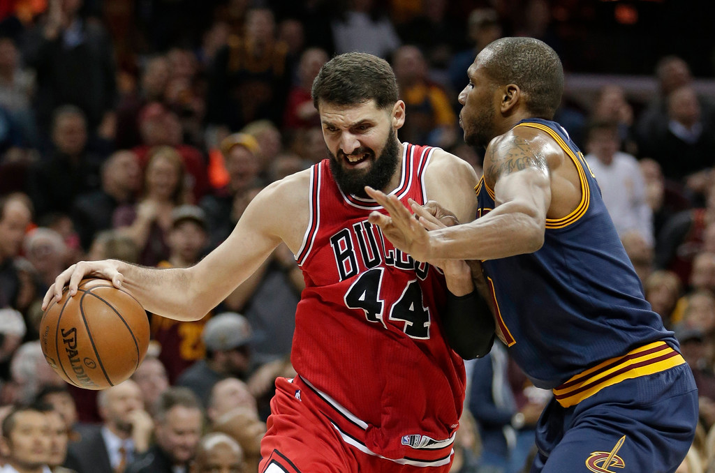 . Chicago Bulls\' Nikola Mirotic (44) drives past Cleveland Cavaliers\' James Jones (1) in the first half of an NBA basketball game, Saturday, Feb. 25, 2017, in Cleveland. (AP Photo/Tony Dejak)