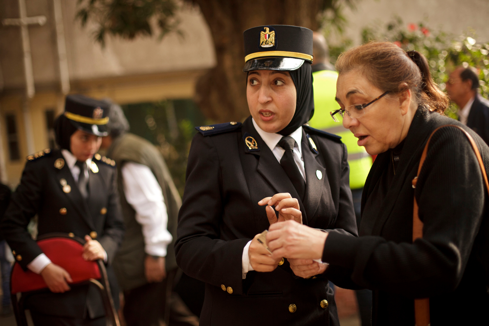 . An Egyptian policewoman directs a woman at a polling site on the first day of voting in the country\'s constitutional referendum in the upscale Zamalek neighborhood of Cairo, Egypt, Tuesday, Jan. 14, 2014. Egyptians voted Tuesday on a draft constitution that represents a key milestone in a military-backed roadmap put in place after the nation\'s Islamist president was overthrown in a popularly backed coup last July.(AP Photo/Maya Alleruzzo)