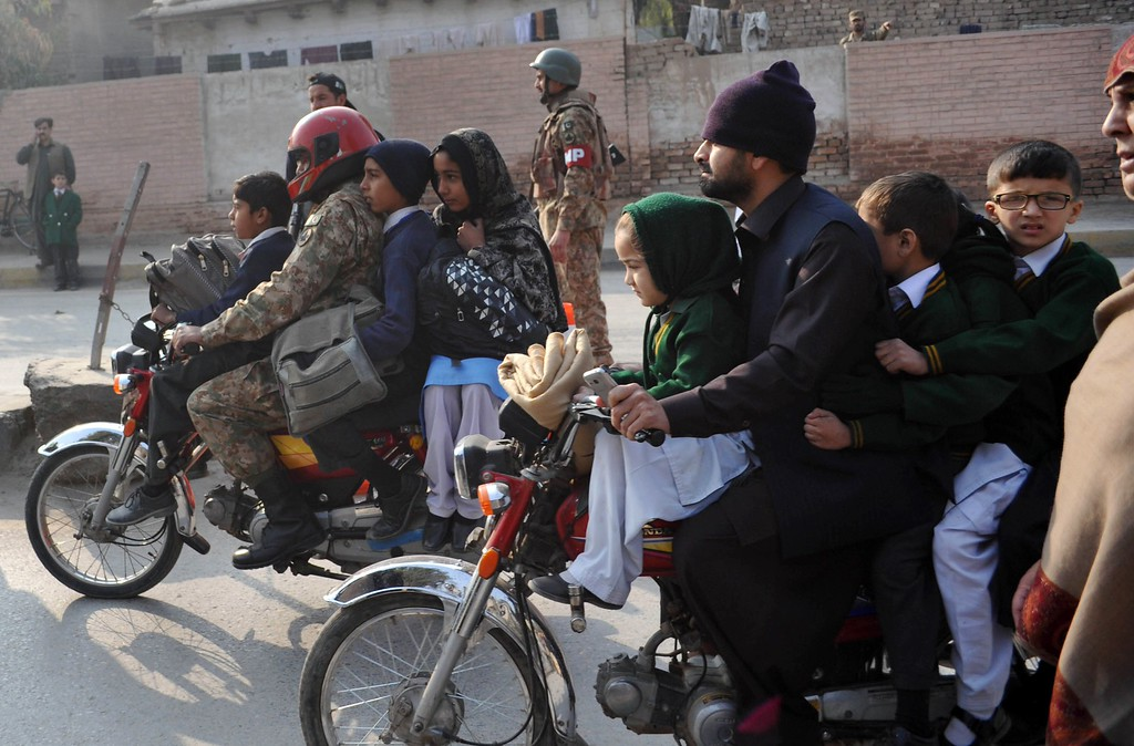 . Pakistani parents leave with their children near the site of an attack by Taliban gunmen on a school in Peshawar on December 16, 2014. Taliban insurgents killed at least 130 people, most of them children, after storming an army-run school in Pakistan December 16 in one of the country\'s bloodiest attacks in recent years. AFP PHOTO/ A Majeed/AFP/Getty Images