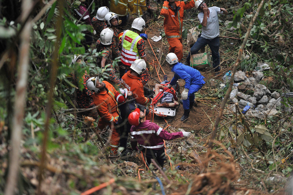 . Malaysian emergency services personnel rescue a passenger, seen on a stretcher, after a passenger bus carrying tourists and local residents fell into a ravine near the Genting Highlands, about an hour\'s drive from Kuala Lumpur, Malaysia, Wednesday, Aug. 21, 2013.  (AP Photo)