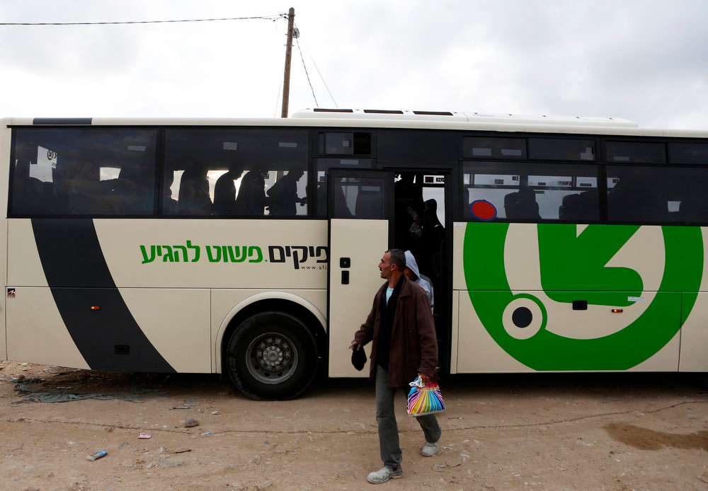 . Laborers disembark a Palestinians-only bus before crossing through Israel\'s Eyal checkpoint as they returns to the West Bank, near Qalqilya March 4, 2013. Israel launched two Palestinians-only bus lines in the occupied West Bank on Monday, a step an Israeli rights group described as racist and which the Transport Ministry called an improvement in service. REUTERS/Baz Ratner