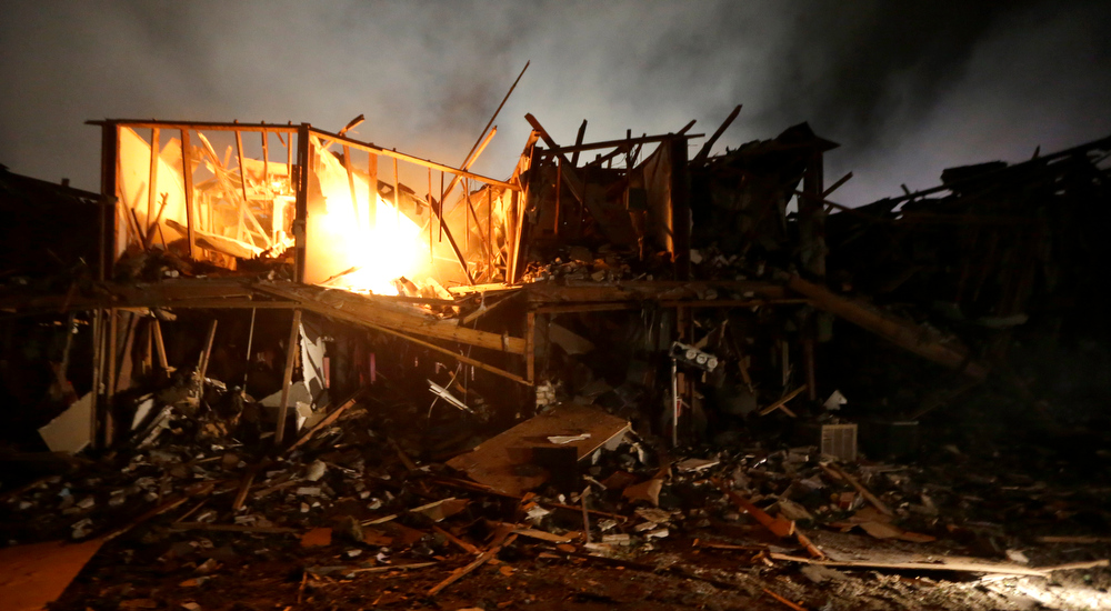 . A fire burns in a apartment complex destroyed near a fertilizer plant that exploded earlier in West, Texas, in this photo made early Thursday morning, April 18, 2013.  (AP Photo/LM Otero)