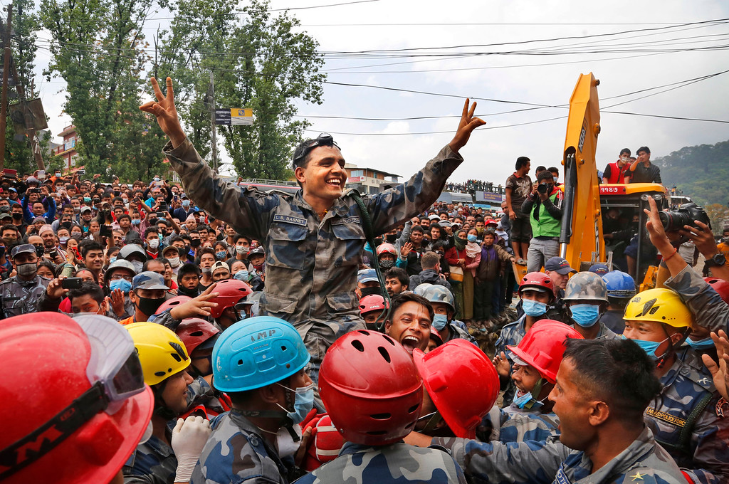 . Nepalese policemen lift their commander and celebrate after they along with U.S. rescuers pulled out Pemba Tamang, a teenage boy from a building that collapsed five days ago in Kathmandu, Nepal, Thursday, April 30, 2015. Crowds cheered Thursday as Tamang was pulled, dazed and dusty, from the wreckage of a seven-story Kathmandu building that collapsed around him five days ago when an enormous earthquake shook Nepal. (AP Photo / Manish Swarup)