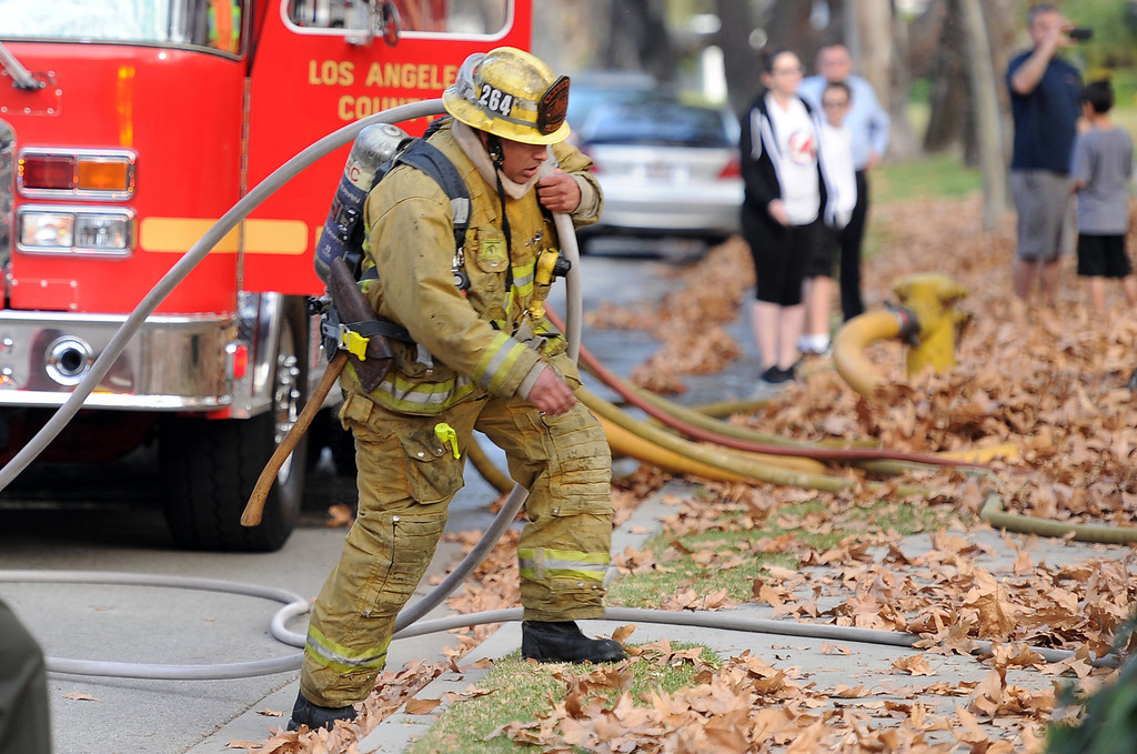 . A Los Angeles County Firefighter carries a water hose as they battle a fire that damaged a single family home. The fire started in the garage along the 1300 block of Via Verde. No injuries, but 5 cars were destroyed including two jaguars in San Dimas, Calif., on Saturday, Jan.4, 2014. 