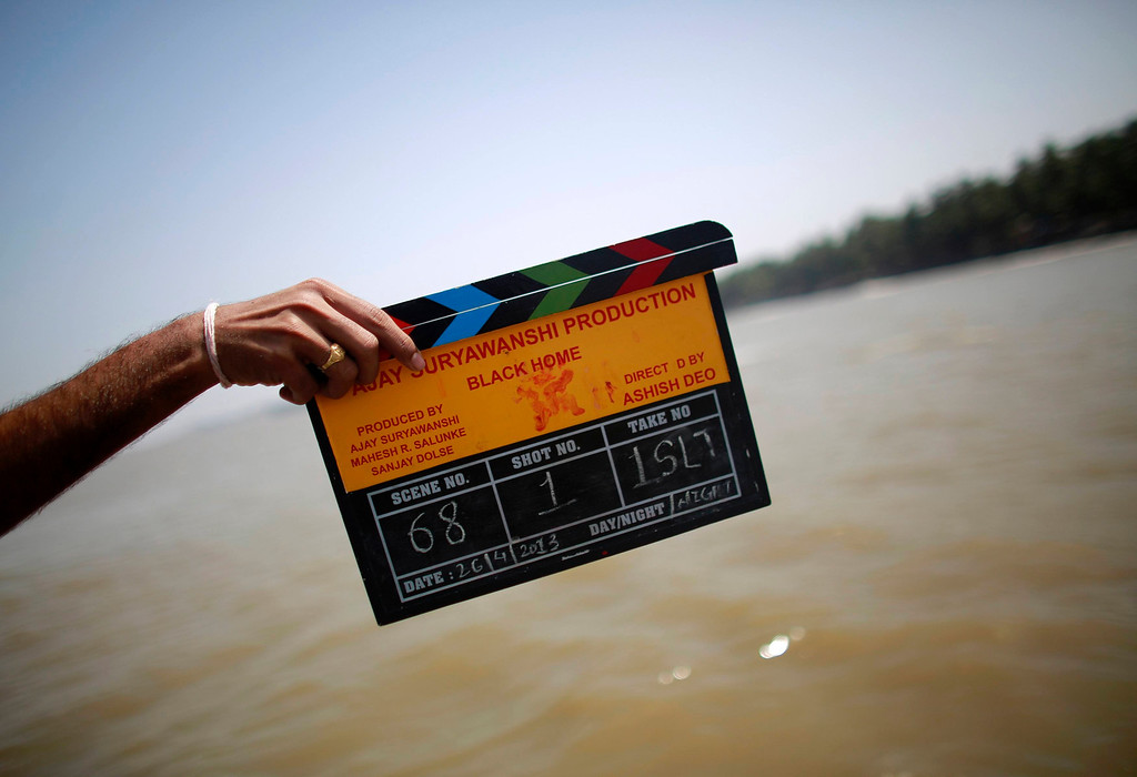 """. A member of a film crew holds a clapper board during the shooting of Bollywood film \'Black Home\' at a beach on the outskirts of Mumbai April 26, 2013. Indian cinema marks 100 years since Dhundiraj Govind Phalke\'s black-and-white silent film \""""Raja Harishchandra\"""" (King Harishchandra) held audiences spellbound at its first public screening on May 3, 1913, in Mumbai. Indian cinema, with its subset of Bollywood for Hindi-language films, is now a billion-dollar industry that makes more than a thousand films a year in several languages. It is worth 112.4 billion rupees (over $2 billion) and leads the world in terms of films produced and tickets sold. Picture taken April 26, 2013. REUTERS/Danish Siddiqui"""