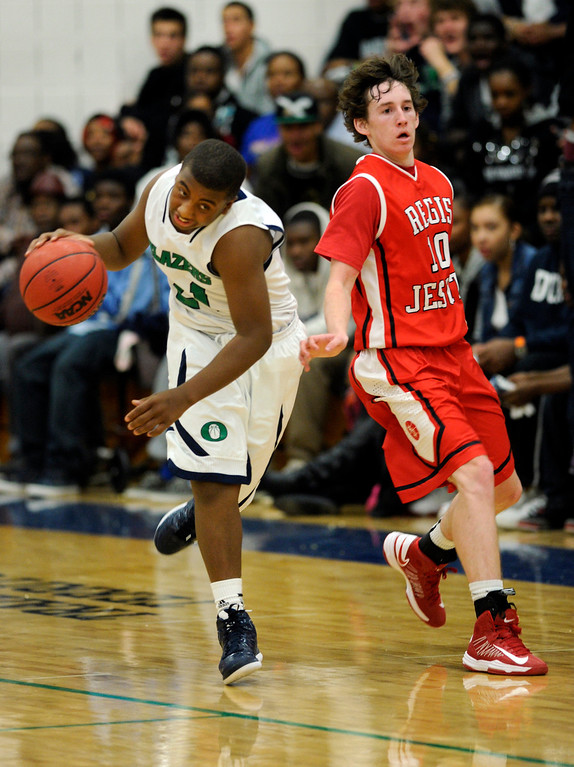 . Blazers guard Reginald Gibson (21) went past Regis guard Eric Stemper (10) in the second half. The Overland High School boy\'s basketball team defeated Regis Jesuit 80-66 Tuesday night, December 11, 2012.  Karl Gehring/The Denver Post