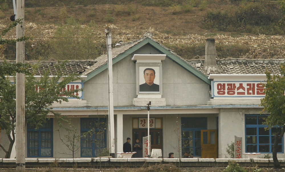 . North Koreans wait at a train station bearing the portrait of the late leader Kim Il-Sung across from the Chinese border town of Tu Men in China\'s northeast Jilin province 12 October 2006.  A collapsing North Korea is a nightmare China hopes will never come true, as it could lead to military and political chaos on its doorstep, analysts said as North Korea\'s declared nuclear test this week highlighted an entire range of violent scenarios, one scarier than the other, and all with direct implications for China\'s national security.  (PETER PARKS/AFP/Getty Images)