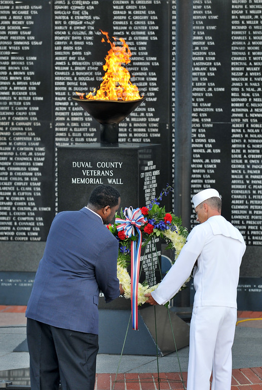 . Guest speaker Eric Josey, left, and Chief Petty Officer Michael Banks lay a wreath in remembrance of the victims of the Sept. 11 terrorist attacks at the Veterans Memorial Wall Thursday, Sept. 11, 2014 in Jacksonville, Fla. Josey is a retired New York City police detective with the SWAT Emergency Services Unit during the attack. (AP Photo/The Florida Times-Union, Will Dickey)
