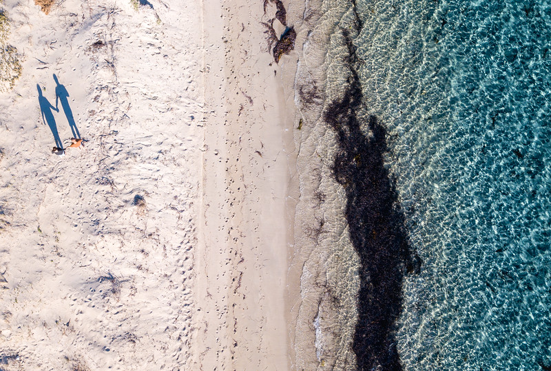 A couple hold hands on a beach in Rockingham, Western Australia.