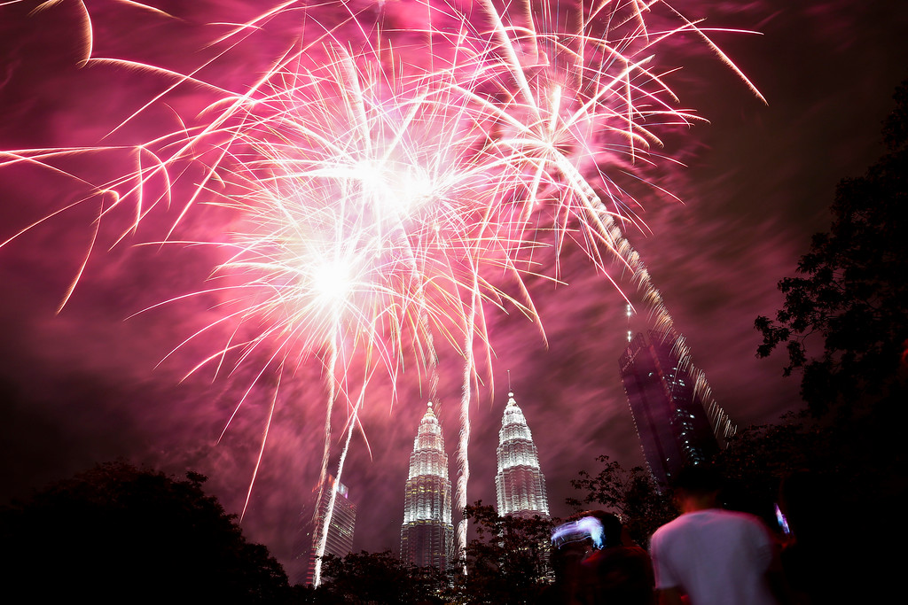 . People watch a fireworks display in front of Malaysia\'s landmark building, the Petronas Twin Towers, during the New Year\'s celebration in Kuala Lumpur, Malaysia, Monday, Jan. 1, 2018. (AP Photo/Sadiq Asyraf)