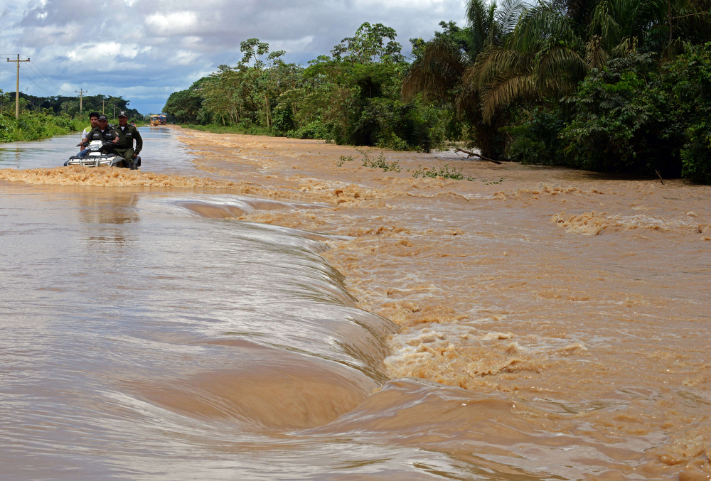 Description of . Policemen drive in a flooded highway, following the overflowing of the Beni river and heavy rains hitting the country, in Reyes, department of Beni, northeast Bolivia, on February 2, 2014. (AIZAR RALDES/AFP/Getty Images)