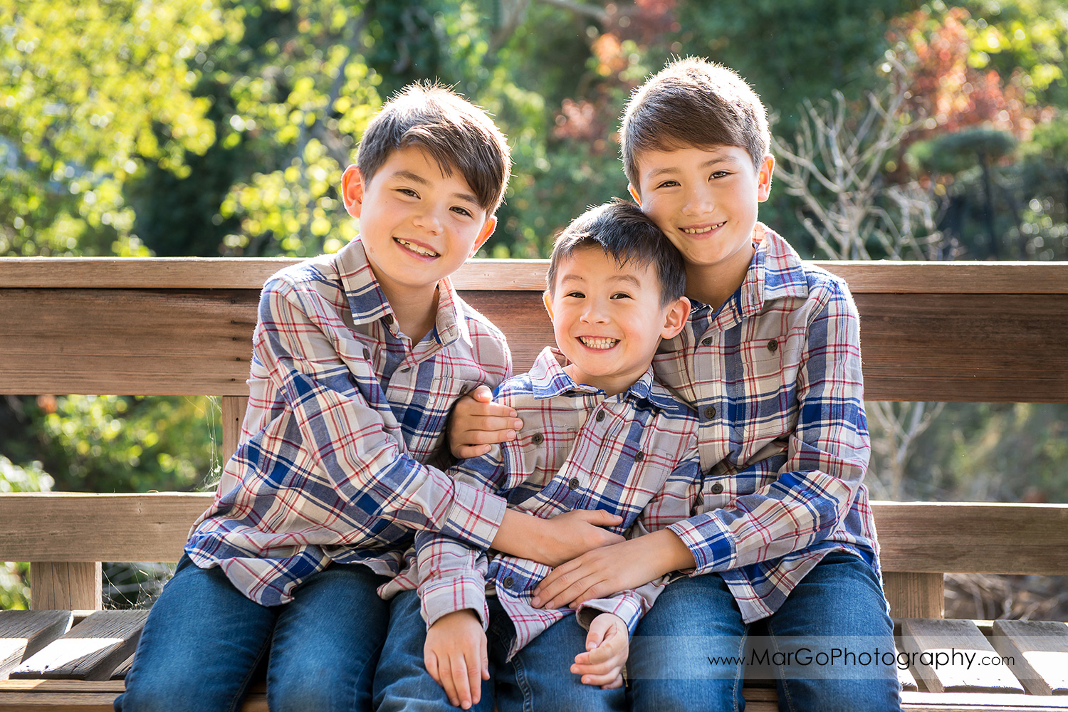 three boys in gray shirts looking into camera sitting on the wood bench at Hayward Japanese Garden