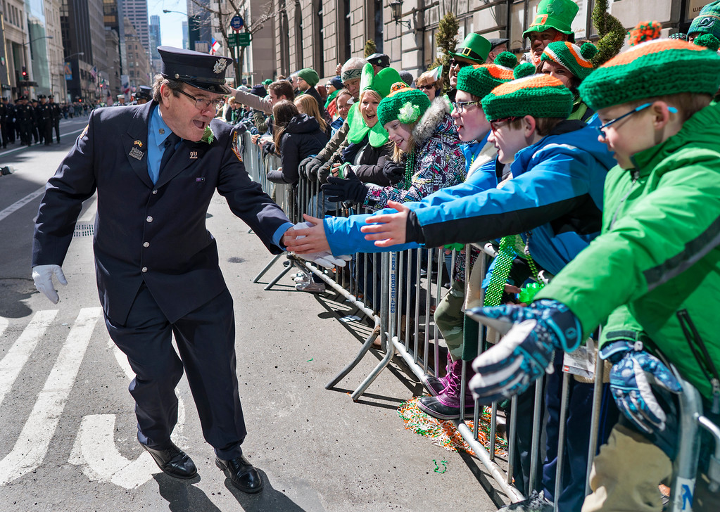 ". A New York City firefighter greets spectators as they take part in the St. Patrick\'s Day parade Saturday, March 17, 2018, in New York.   Several bagpipe bands led a parade made up of over 100 marching bands after Democratic Gov. Andrew Cuomo spoke briefly, calling it a ""day of inclusion\"" and adding: \""We\'re all immigrants.\""  (AP Photo/Craig Ruttle)"