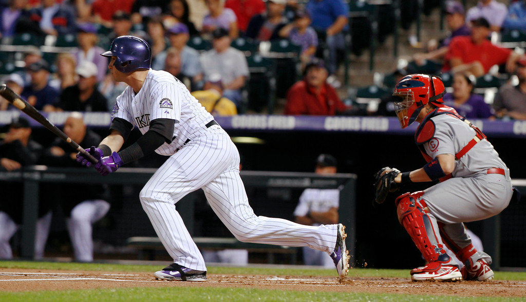 . Colorado Rockies\' Troy Tulowitzki, left, follows the flight of his two-run single in front of St. Louis Cardinals catcher Yadier Molina in the first inning of a baseball game in Denver on Wednesday, Sept. 18, 2013. (AP Photo/David Zalubowski)