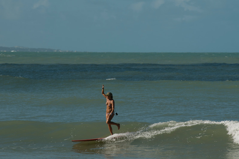 A female surfer prcticing tricks on a longboard, Praia do Pipa, Rio Grande du Norte, Brazil.