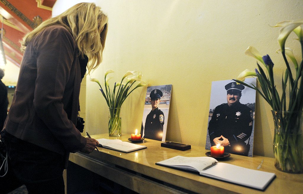 . A memory diary for both Elizabeth Butler and Sgt. Loran \'Butch\' Baker was left for guests to sign at the Del Mar Theatre Thursday afternoon where the memorial service was being live broadcast from the HP Pavilion in San Jose (Matthew Hintz/Sentinel).