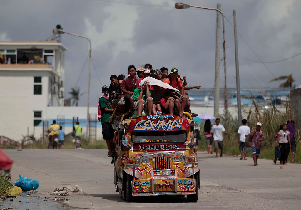 . Survivors ride an overloaded passenger jeepney as they flee typhoon-hit Tacloban city, Leyte province, central Philippines on Wednesday, Nov. 13, 2013. Typhoon Haiyan, one of the strongest storms on record, slammed into six central Philippine islands on Friday leaving a wide swath of destruction. (AP Photo/Aaron Favila)