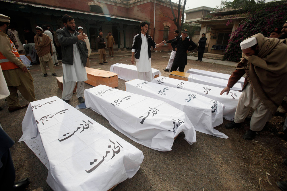. People gather around coffins of victims killed during a bomb attack at Fauji Market in Peshawar December 17, 2012. The blast in the market in northwest Pakistan on Monday killed at least 15 people, a security official said. The official said at least 20 people had been wounded in the blast in the market in the Khyber region, near the border with Afghanistan, and the death toll could rise.  REUTERS/Fayaz Aziz