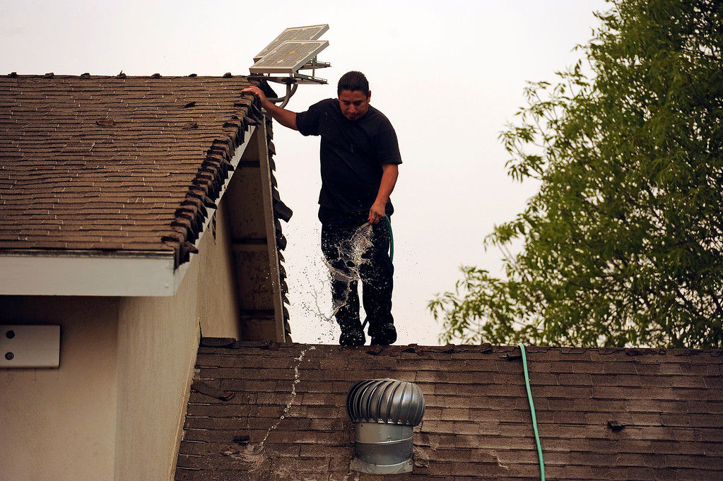 . Victor Noriega uses a hose on the roof of a friends home on Rotella St as flames from the Springs Fire approach in Thousand Oaks Friday, May 3, 2013. (Hans Gutknecht/LA Daily News)