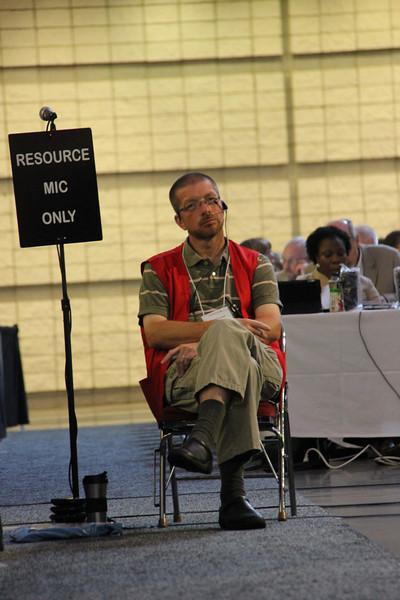 A volunteer waits to assist voting members.