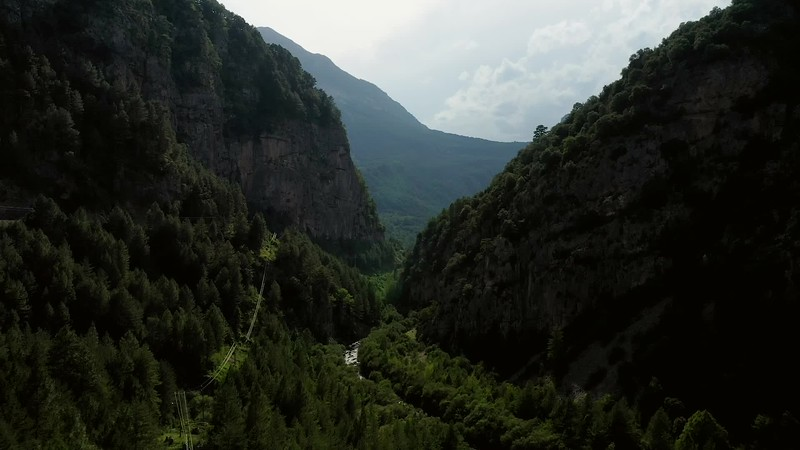 Available in 4k - Aerial travelling shot flying through the Desfiladero de La Inclusa, Valle de Gistain in Aragon. With the high canyon rocks around and rio Cinqueta until Embalse de Plandescún