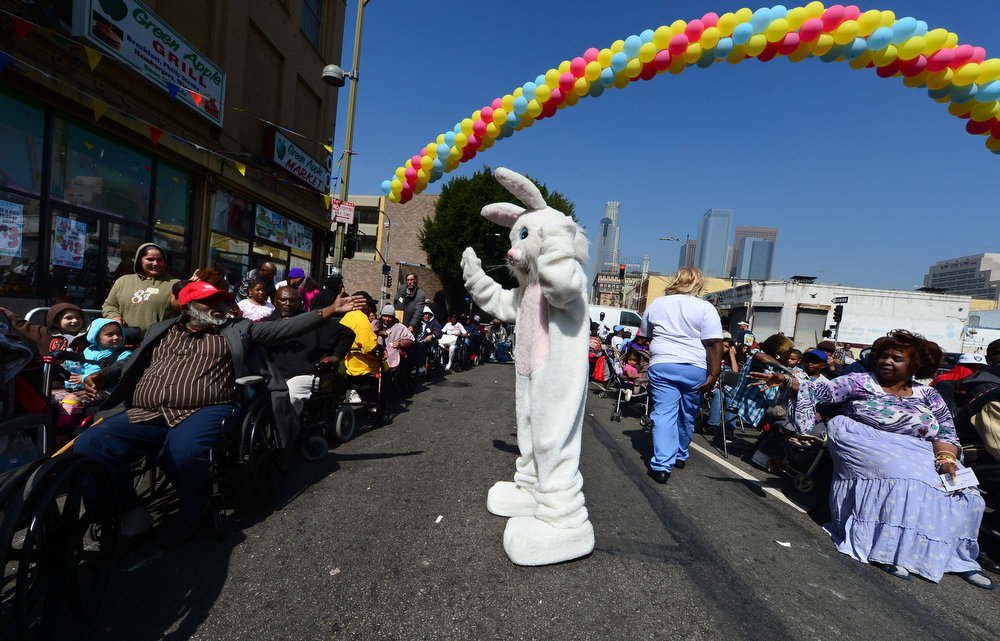 . Hands reach out to touch a person dressed as the Easter Bunny as people attend the Los Angeles Mission\'s Good Friday event on Skid Row on March 29, 2013 in Los Angeles, California. Celebrities and volunteers joined together in giving something back to this community of the homeless, among the largest in the US, who were fed a fully-prepared meal and had the opportunity to be given foot washing and hygiene kits. Foot washing, a symbolic ritual of humbleness and respect derived from Jesus Christ\'s washing of his disciples feet at the Last Supper, was offered by the Los Angeles Health Center and  volunteers. AFP PHOTO/Frederic J. BROWN